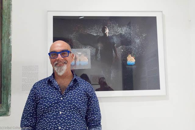 """ישראל אהרוני לצד תמונתו בתערוכה """"כנפיים"""""""