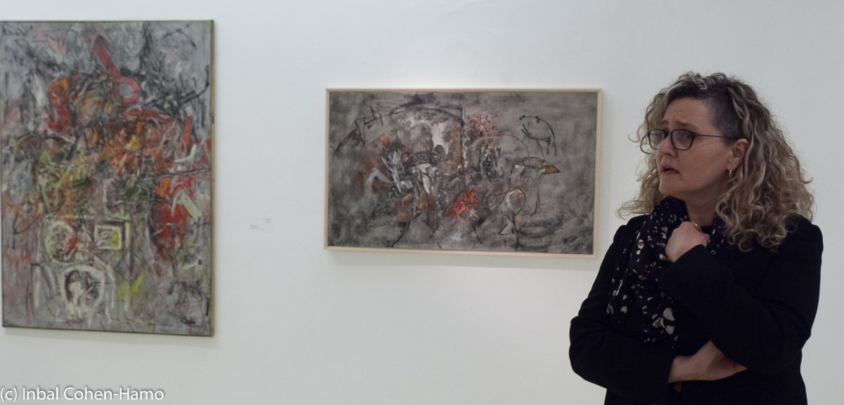 האוצרת איה לוריא ליד ציוריו המופשטים המוקדמים של ליפשיץ. צילום: ענבל כהן חמו