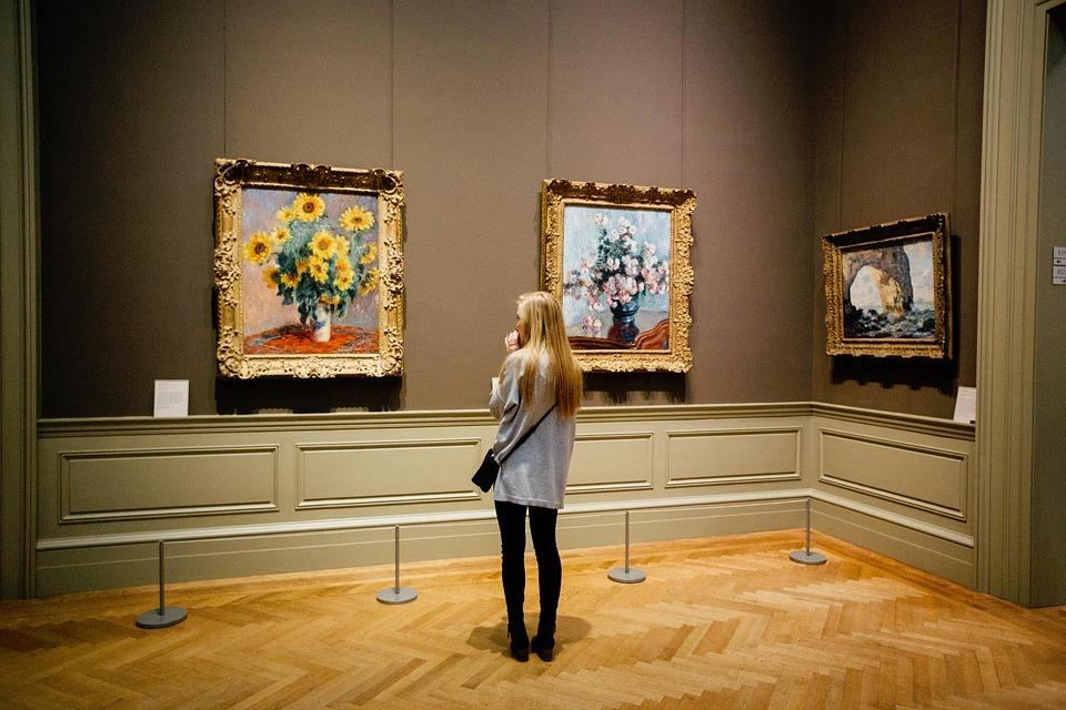 אישה עומדת במוזיאון ומסתכלת על תמונות - רעיון לבילוי חינם