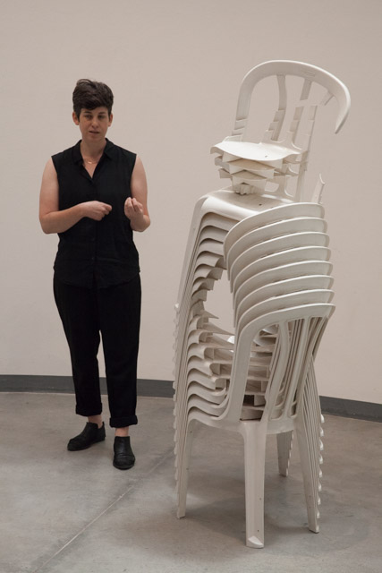הילה כהן-שניידרמן ליד פסל של אוריאל מרון מכסאות פלסטיק