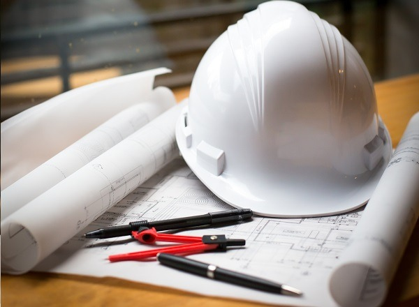 construction concept image helmet rolled blueprints on wooden bo