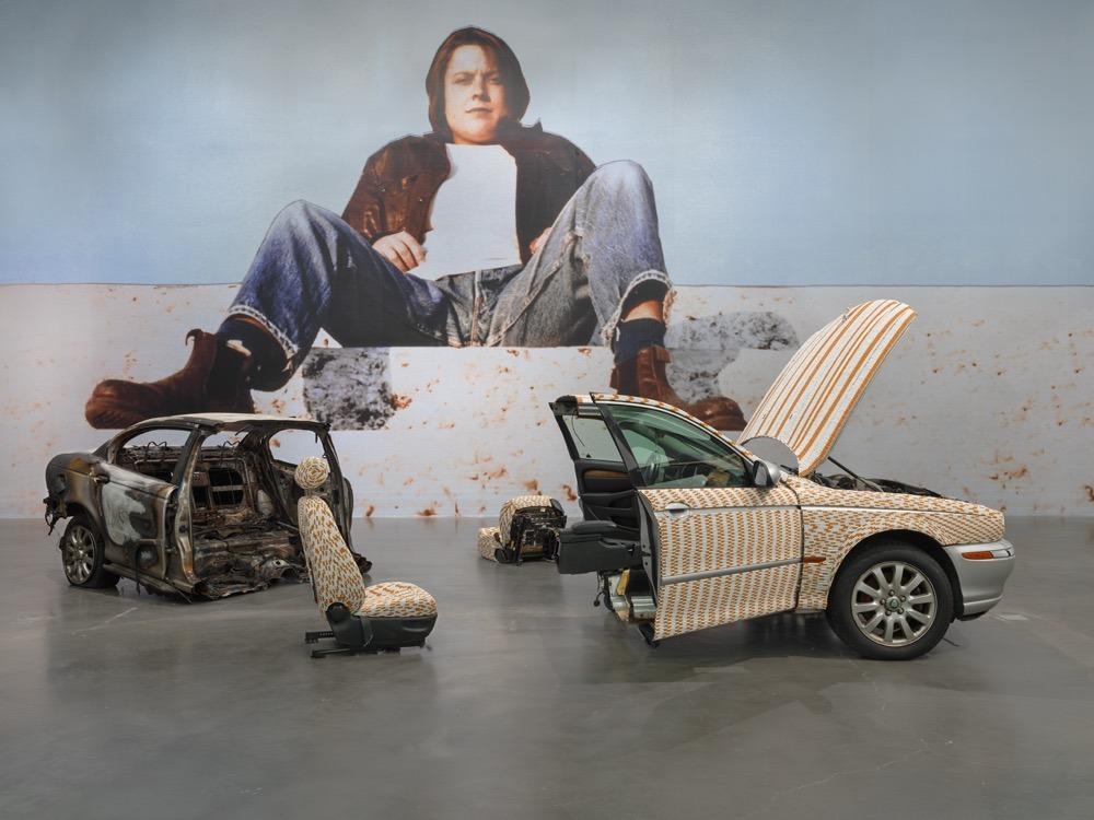 שרה לוקאס. דיוקן עצמי על קיר שלם, מעל למיצב של מכונית שכולה מצופה... נו, מזהים?
