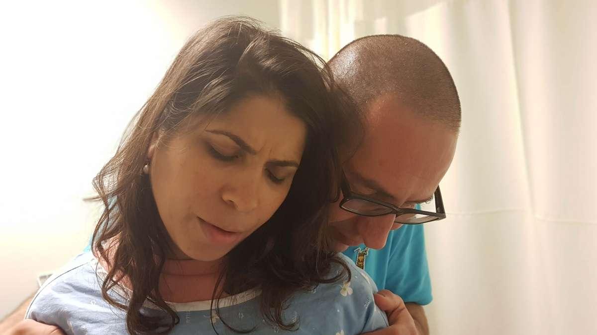 אשה במהלך ציר נתמכת על ידי בן זוגה