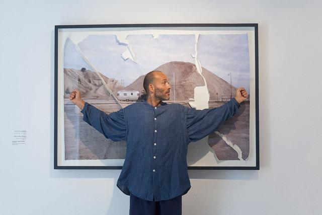גרגורי אבו מדגים את גודל הצילום שהדפיס, כזה שיכול היה לפרוס בין שתי ידיו. צילום: ענבל כהן חמו