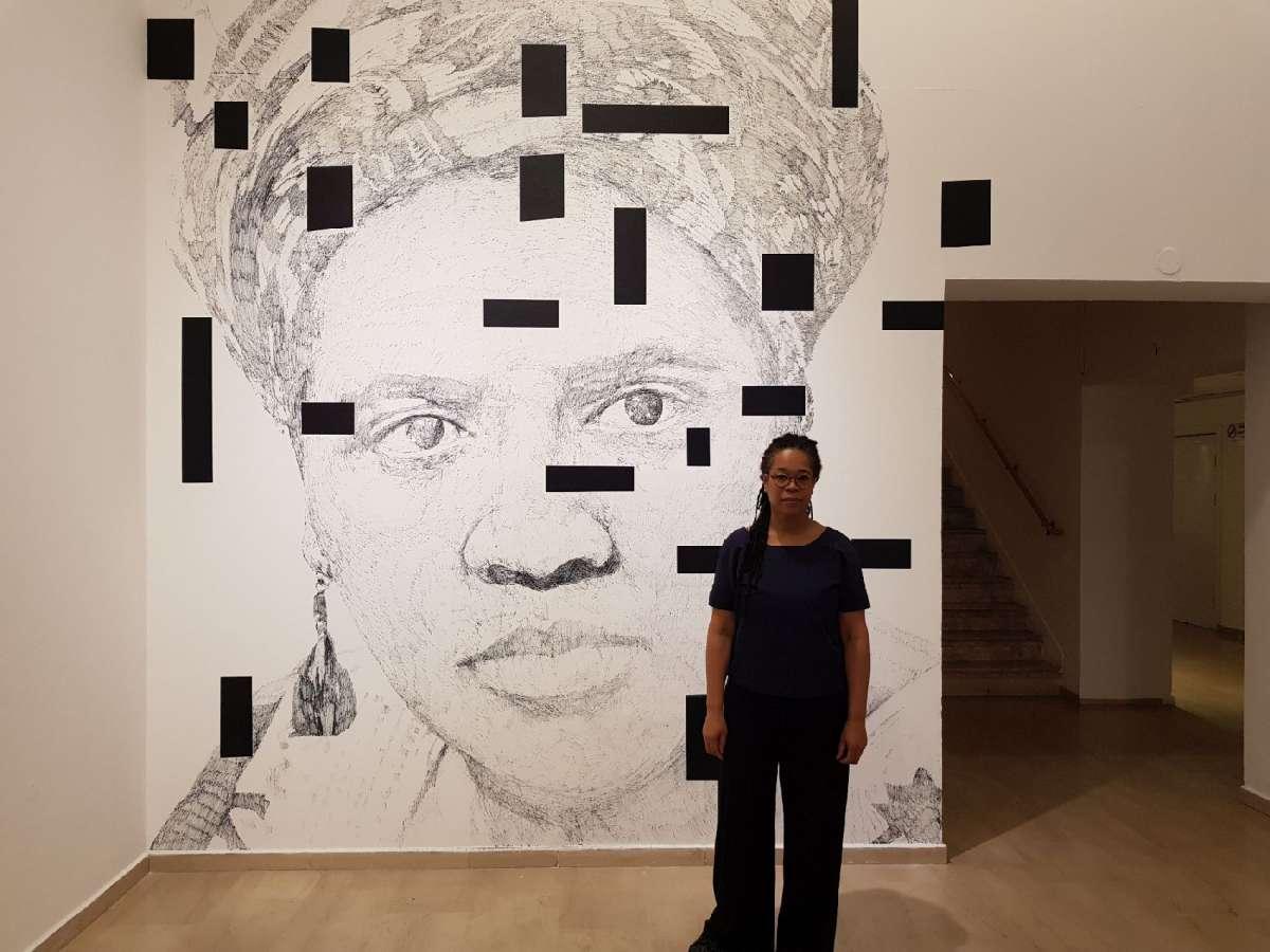 איריס קנסמיל על רקע הרישום בכניסה צילום קרן פרגו