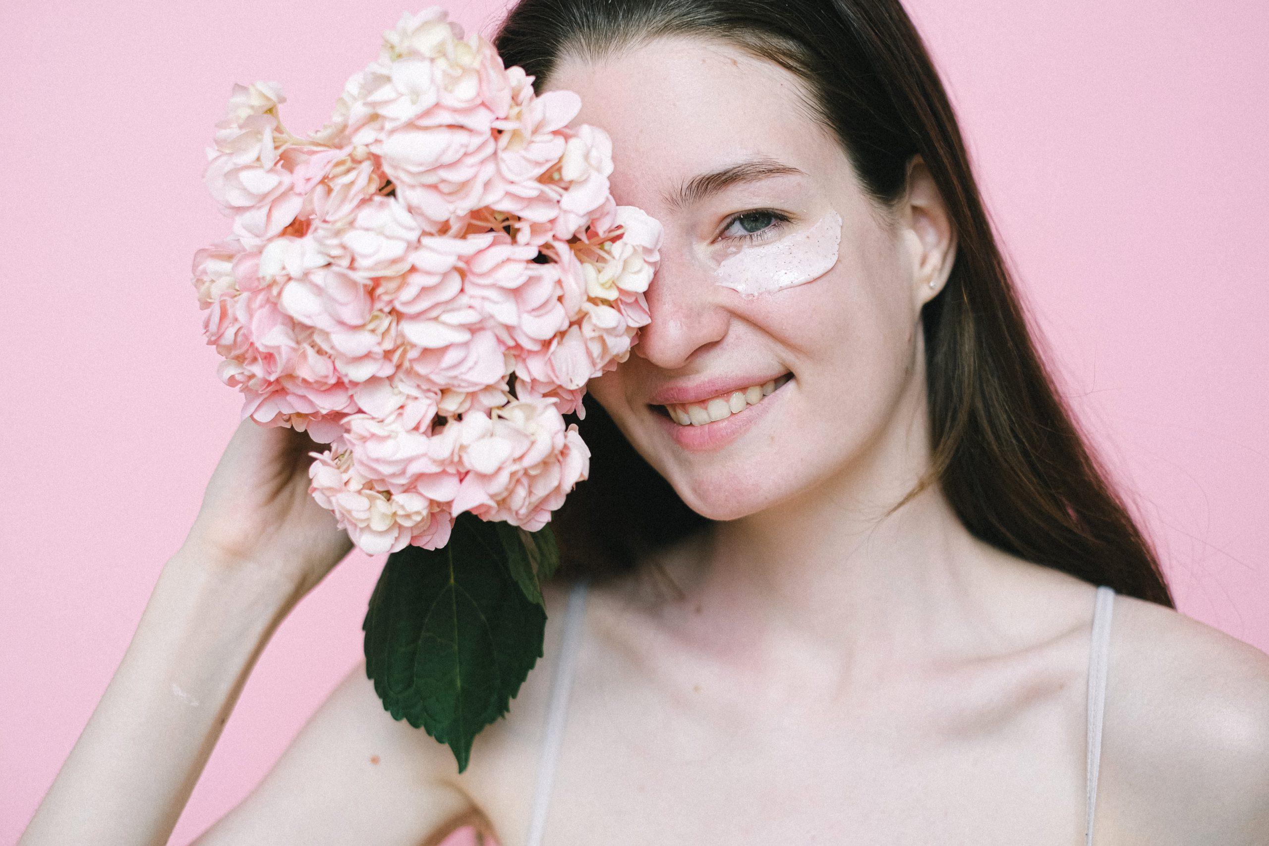 אישה מחזיקה זר פרחים ורוד ויש לה קרם מתחת לעיניים