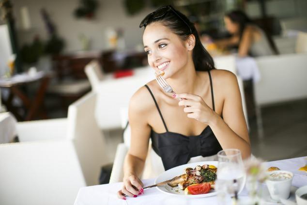 בחורה אוכלת במסעדה