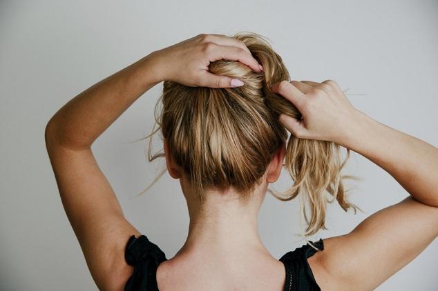 אשה אוספת שיער shutterstock  By BOKEH STOCK