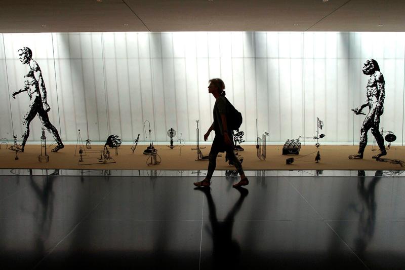 """סטיל מתוך """"המוזיאון"""" - אשה עוברת לפני התערוכה """"אבולוציה"""""""